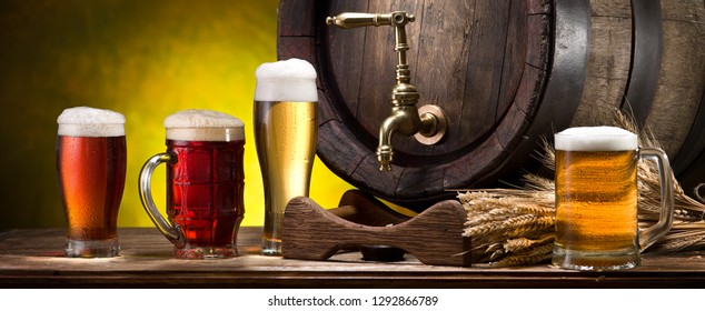 Glasses of beer and beer cask on the wooden table. Craft brewery.
