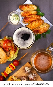 Glasses of beer with chicken wings, burger, meat balls, grilled corn and vegetables. Beer bites. Ale and food still life. View from above, top studio shot