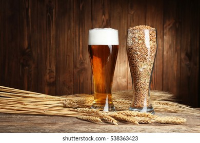 Glasses of beer and seeds with spikes on wooden background
