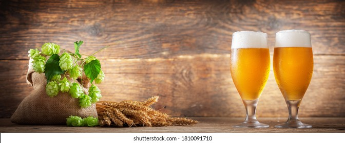 glasses of beer, wheat ears, hops on a wooden background
