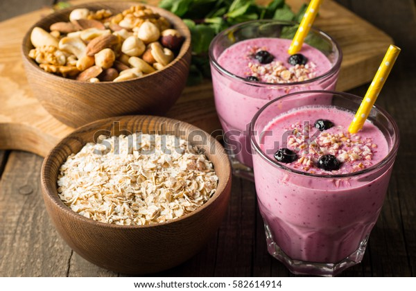 Glasses of berry smoothie with nuts, mint, blueberry, blackberry, raspberry, and yougurt on wooden table. Weight loss and diet concept.