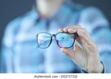 Glasses with black optics are held in hand. Selection of glasses for vision concept