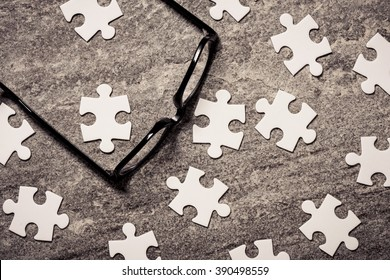 Glasses and blank puzzel pieces. Concept of business challenge, teamwork and solution.