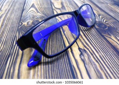 glasses with blue frame on wooden wood