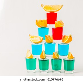 Glasses with blue, green and red kamikaze, glamorous drinks, mixed drink poured into shot glasses, party set