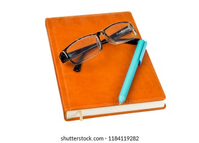 Glasses, blue pencil and orange leather notebook journal isolated on white background.