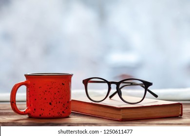 glasses, a book and a mug on a wooden window sill, in winter, copy space