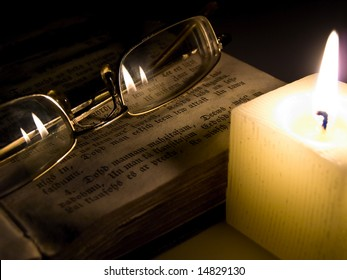 glasses at the book near candle in the night