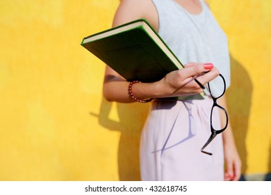 glasses and book on a hand