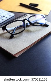 glasses and book on wooden table. film colors tone and soft-focus in the background. over light