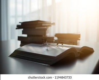 glasses with a book is opening on desk table