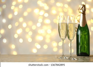Glasses and bottle of champagne on table against blurred lights. Space for text