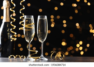 Glasses and bottle of champagne with serpentine streamers against blurred lights on black background. Space for text