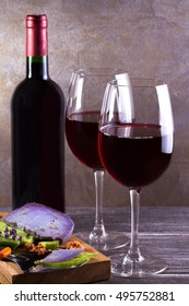 Glasses and bottle red  wine with lavender, pesto cheese and grape on chopping board. Wine and food still life