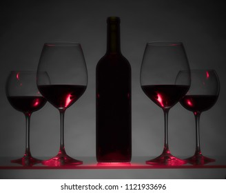 Glasses and bottle of red wine on a dark background.