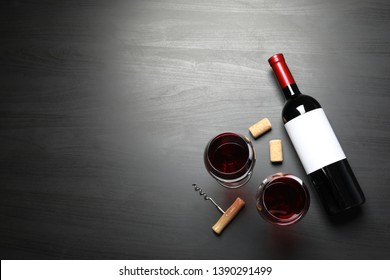 Glasses and bottle with red wine on dark background, flat lay. Space for text