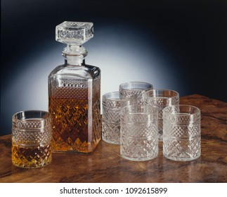 glasses and bottle set for whiskey, dark background, wooden table