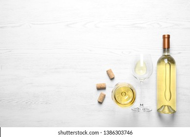 Glasses and bottle with white wine on wooden background, flat lay. Space for text