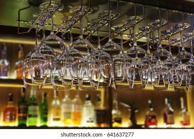 Glasses and bottles of alcoholic drinks on the bar before the party.