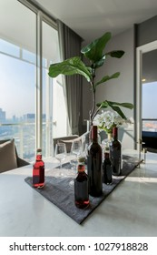 Glasses, bottles of  champange wine  at rooftop restaurant with view of modern city skyline background, luxury romantic dinner for couple.