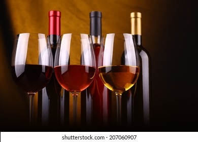 Glasses and bottles of red, rose and white wine over a draped background lit yellow