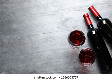 Glasses and bottles with red wine on color background, flat lay. Space for text