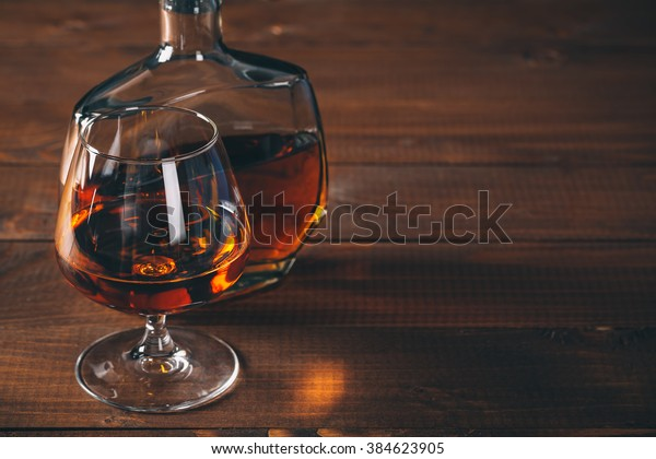 Glasses of brandy or cognac and bottle on the wooden table.