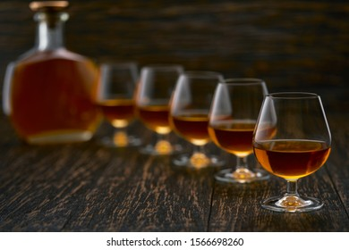 glasses of  brandy on a wooden table with the silhouette of a bottle of brandy.