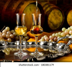 Glasses of brandy set in a cellar with barrels of reserves