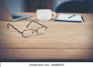 Glasses of Business workspace on wooden table.