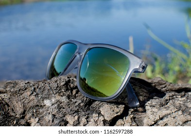 glasses by the river on the grass