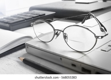 Glasses, calculator, computer. On the table