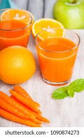 Glasses with carrot juice, apple, mint leaf and sliced orange