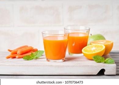 Glasses with carrot juice, apple, sliced orange and mint leaf