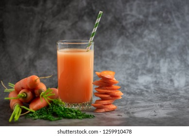 Glasses of carrot juice with vegetables on grey table. Side view.