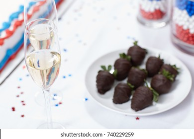 Glasses of champagne against cake and chocolate strawberries on table at election rally