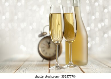 Glasses of champagne and alarm clock on silver background
