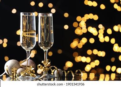 Glasses of champagne, Christmas decor and serpentine streamers against black background with blurred lights. Space for text