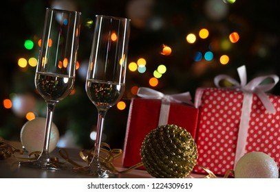 Glasses of champagne and Christmas gifts and balls on the festive background