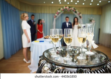 Glasses of champagne, civil wedding ceremony on background. Shallow depth of field. Selective focus.