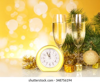 Glasses of champagne with a clock and Christmas decorations on a yellow background