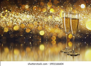 Glasses with champagne and copy space for text on blurred yellow lights.