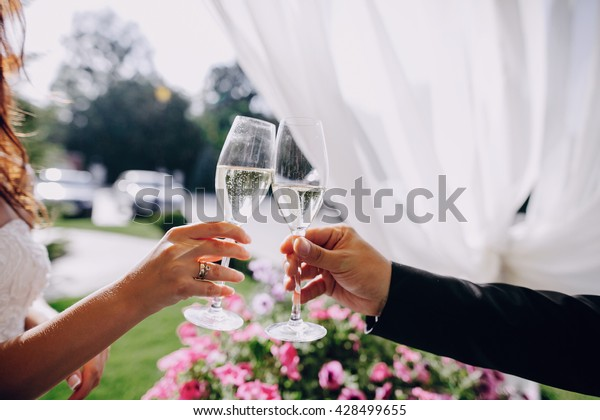glasses with champagne in the hands of a beautiful wedding couple
