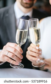 glasses with champagne in hands of bride and groom