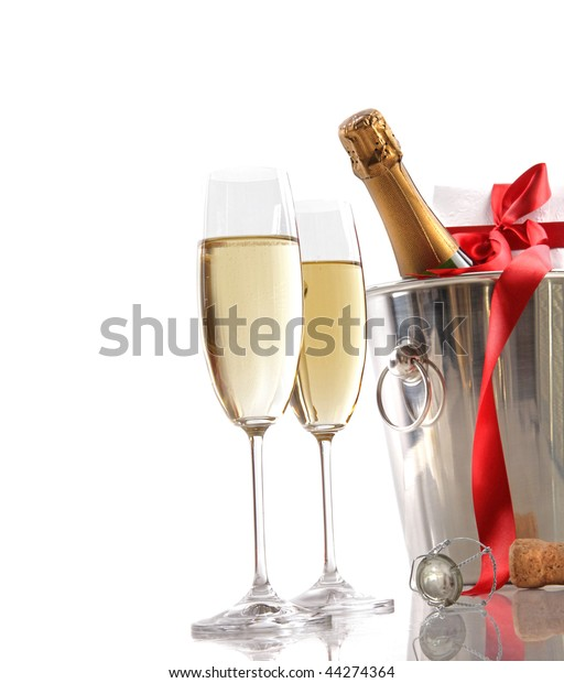 Glasses of champagne and ice bucket with red ribbon gift