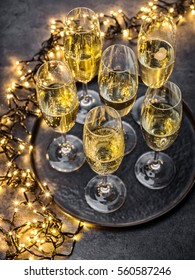 glasses of champagne and lights on dark grey table