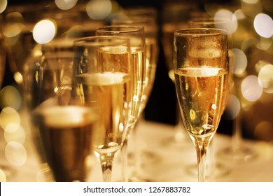 Glasses of champagne with many visible bubbles on a table with blurred background of festive lights. Celebration concept.