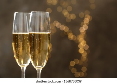 Glasses of champagne on blurred background, closeup. Space for text