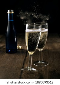 glasses of champagne on a dark background with bokeh in the form of stardust