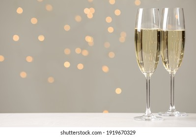Glasses of champagne on grey table against blurred lights. Space for text